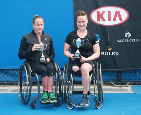 finalists: MELBOURNE, AUSTRALIA - JANUARY 30, 2016:Grand Slam finalists Jiske Griffioen  L and Aniek Van Koot of Netherlands posing with trophy after Australian Open 2016 women s wheelchair doubles final match Editorial