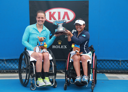 doubles: MELBOURNE, AUSTRALIA - JANUARY 30, 2016: Marjolein Buis of Netherlands L and Yui Kamiji of Japan posing with trophy after victory Australian Open 2016 women s wheelchair doubles final match