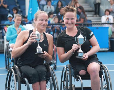 30 s: MELBOURNE, AUSTRALIA - JANUARY 30, 2016:Grand Slam finalists Jiske Griffioen  L and Aniek Van Koot of Netherlands posing with trophy after Australian Open 2016 women s wheelchair doubles final match Editorial