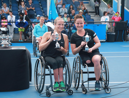 doubles: MELBOURNE, AUSTRALIA - JANUARY 30, 2016:Grand Slam finalists Jiske Griffioen  L and Aniek Van Koot of Netherlands posing with trophy after Australian Open 2016 womens wheelchair doubles final match Editorial