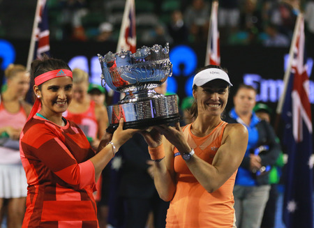 racket stadium: MELBOURNE, AUSTRALIA - JANUARY 30, 2016: Grand Slam champion Sania Mirza of India L and  Martina Hingis of Switzerland during trophy presentation after doubles final match at Australian Open 2016