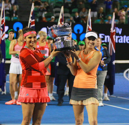 doubles: MELBOURNE, AUSTRALIA - JANUARY 30, 2016: Grand Slam champion Sania Mirza of India L and  Martina Hingis of Switzerland during trophy presentation after doubles final match at Australian Open 2016