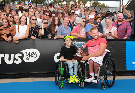 racket stadium: MELBOURNE, AUSTRALIA - JANUARY 30, 2016: Grand Slam champion Dylan Alcott of Australia posing with trophy with fans after Australian Open 2016 quad wheelchair singles final match in Melbourne Park Editorial