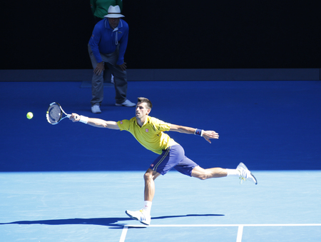racket stadium: MELBOURNE, AUSTRALIA - JANUARY 24, 2016: Eleven times Grand Slam champion Novak Djokovic of Serbia in action during his round 4 match at Australian Open 2016  at Rod Laver Arena in Melbourne Park Editorial