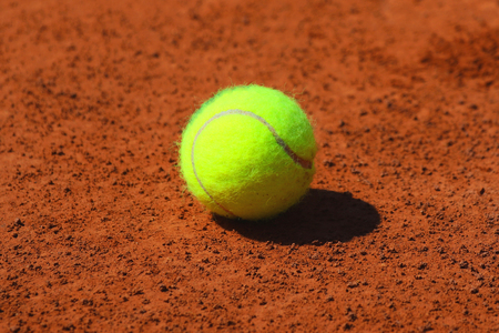 red clay: Tennis ball at red clay tennis court