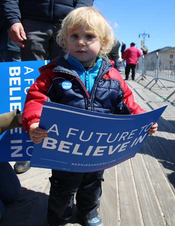 senate elections: NEW YORK - APRIL 10, 2016: Young Bernie Sanders supporter during presidential candidate Bernie Sanders rally  at iconic Coney Island boardwalk in Brooklyn, New York