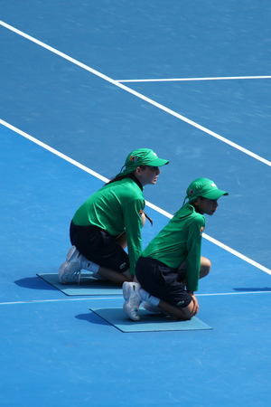 racket stadium: MELBOURNE, AUSTRALIA - JANUARY 26, 2016: Ball boys in action during match at Australian Open 2016 in Melbourne Park Editorial