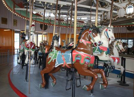 coney: BROOKLYN, NEW YORK - MAY 14, 2016: Horses on a traditional fairground B&B carousel at historic Coney Island Boardwalk in Brooklyn