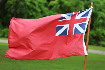 merchant: The British Merchant Navy Red Ensign flag for civilian fleet. The Red Ensign or Red Duster is a flag that originated in the early 17th century as an English ensign flown by the Royal Navy Stock Photo