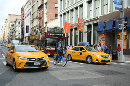NEW YORK - MARCH 10, 2016: New York City Taxi and Citibike rider in Soho, Lower Manhattan Editorial
