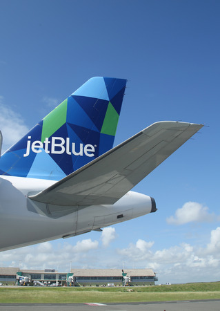 jetblue: PUNTA CANA, DOMINICAN REPUBLIC - JANUARY 4, 2016: JetBlue Airbus A321 prism inspired design tailfin at Punta Cana International Airport