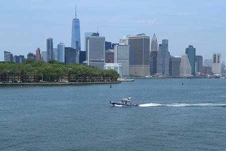 NEW YORK - MAY 26, 2016: NYPD boat providing security during Fleet Week 2016 in New York Harbor. Manhattan Sky Line on the background