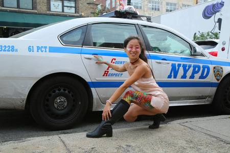 NEW YORK, - JUNE 4, 2016: Unidentified model posing in the front of NYPD police car during Bushwick Collective Block Party in Brooklyn, New York Reklamní fotografie - 57926780