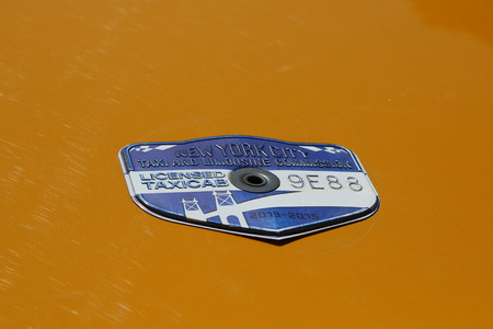 NEW YORK - MARCH 29, 2015: New York City taxi medallion in New York. Canary yellow in color, medallion taxis are able to pick up passengers anywhere in the five boroughs. 版權商用圖片 - 58003069