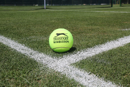 NEW YORK - AUGUST 6, 2015: Slazenger Wimbledon Tennis Ball on grass tennis court. Slazenger Wimbledon Tennis Ball exclusively used and endorsed by The Championships, Wimbledon