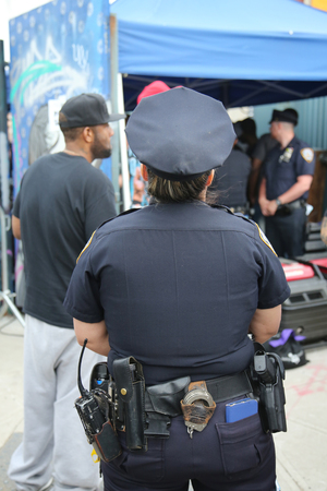 collective: NEW YORK - JUNE 4, 2016: NYPD officer providing security at Hip Hop concert during  Bushwick Collective Block Party in Brooklyn