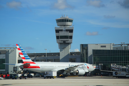 MIAMI, FLORIDA - JUNE 1, 2016: American Airlines plane and Air Traffic Control Tower at Miami International Airport. American Airlines operates 274 flights every day from Miami Editorial