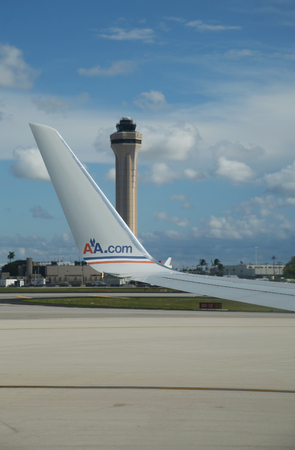 operates: MIAMI, FLORIDA - JUNE 1, 2016: American Airlines plane and Air Traffic Control Tower at Miami International Airport. American Airlines operates 274 flights every day from Miami Editorial