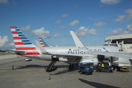 american airlines: MIAMI, FLORIDA - JUNE 1, 2016: American Airlines baggage handlers uploading luggage at Miami International Airport. American Airlines operates 274 flights every day from Miami
