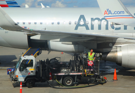 operates: MIAMI, FLORIDA - JUNE 1, 2016: American Airlines worker refueling plane at Miami International Airport. American Airlines operates 274 flights every day from Miami Editorial