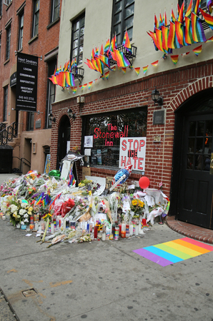outside shooting: NEW YORK - JUNE 16, 2016: Memorial outside the gay rights landmark Stonewall Inn for the victims of the mass shooting in Pulse Club, Orlando in New York City