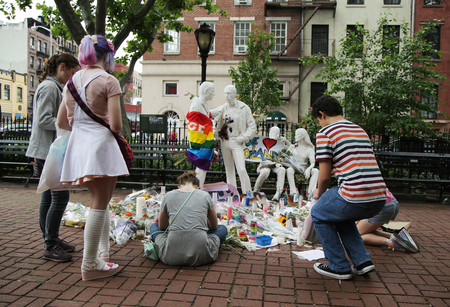 dangerous love: NEW YORK - JUNE 16, 2016: Mourners honor Orlando massacre victims at the Gay Liberation Memorial in Christopher Park in New York City