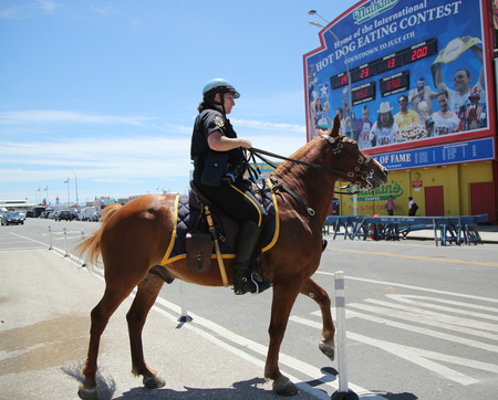 police unit: NEW YORK - JUNE 16, 2016: NYPD Mounted Unit police officer providing security at Coney Island in Brooklyn, New York
