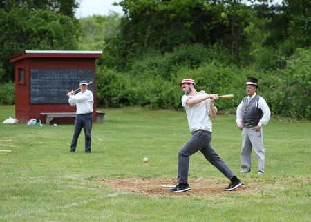 outfield: OLD BETHPAGE, NEW YORK - MAY 22, 2016: Baseball team in 19th century vintage uniform during old style base ball play following the rules and customs from 1864 in Old Bethpage Village Restoration Editorial