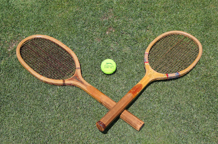 wimbledon: NEW YORK - JUNE 30, 2016: Vintage Tennis rackets and Slazenger Wimbledon Tennis Ball on grass tennis court. Slazenger Wimbledon Tennis Ball exclusively used and endorsed by The Championships, Wimbledon Editorial