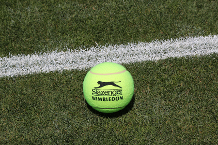 wimbledon: NEW YORK - JUNE 30, 2016: Slazenger Wimbledon Tennis Ball on grass tennis court. Slazenger Wimbledon Tennis Ball exclusively used and endorsed by The Championships, Wimbledon