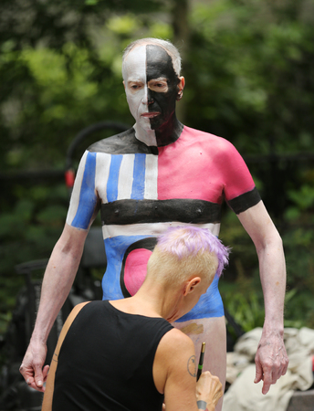 NEW YORK - JULY 9, 2016: Artists paint 100 fully nude models of all shapes and sizes during third NYC Body Painting Day in midtown Manhattan featuring artist Andy Golub in New York