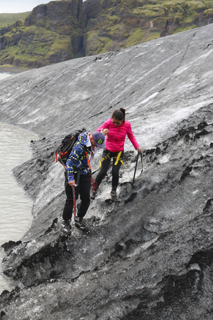 guia turistico: ICELAND - JULY 4, 2016: Tour guide helping tourist during glacier walk at Solheimajokull glacier. Solheimajokull glacier is one of the biggest glaciers in Europe.