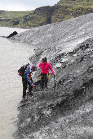 guia turistico: ISLANDIA - 4 de julio, 2016: La guía turística ayudar turística durante la caminata glaciar en Solheimajokull glaciar. Solheimajokull glaciar es uno de los glaciares más grandes de Europa. Editorial