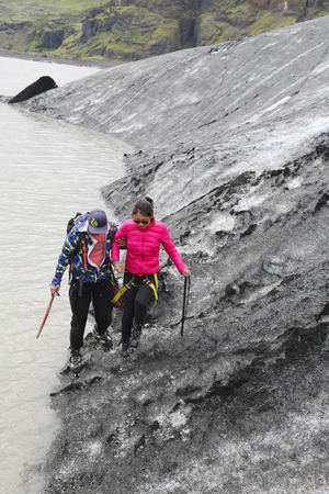 tour guide: ICELAND - JULY 4, 2016: Tour guide helping tourist during glacier walk at Solheimajokull glacier. Solheimajokull glacier is one of the biggest glaciers in Europe.