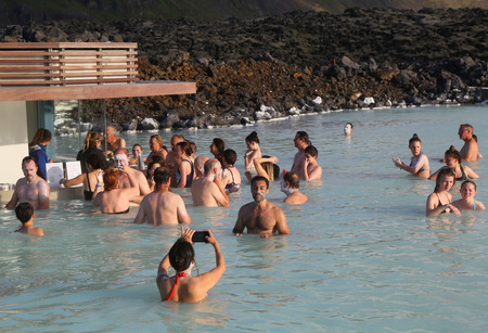 therapy geothermal: ICELAND - JULY 5, 2016: Geothermal spa visitors with silica mud masks relax and refresh at the famous Blue Lagoon in Iceland Editorial