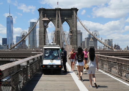 police force: NEW YORK - JULY 19, 2016: NYPD provides security at the Brooklyn Bridge. The New York Police Department, established in 1845, is the largest police force in USA