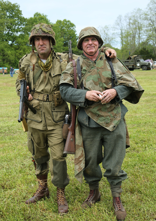 encampment: OLD BETHPAGE, NEW YORK - MAY 22, 2016: World War II Encampment participants in World War II American Army (L) and German Army uniform in Old Bethpage, NY Editorial