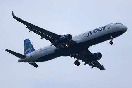 jetblue: NEW YORK - JULY 28, 2016: JetBlue Airways Our 200th Aircraft Livery Airbus A320 descending for landing at JFK International Airport in New York
