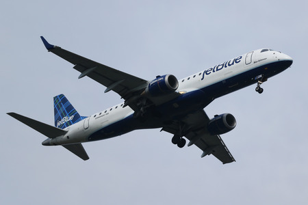 jetblue: NEW YORK - JULY 28, 2016: JetBlue Airways Embraer 190 descending for landing at JFK International Airport in New York