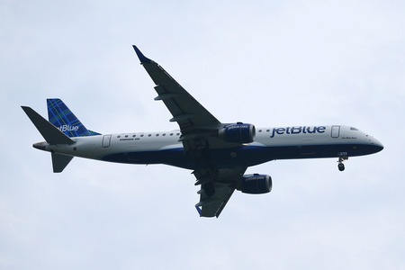 jetblue: NEW YORK - JULY 28, 2016: JetBlue Airways Embraer 190 descending for landing at JFK International Airport in New York