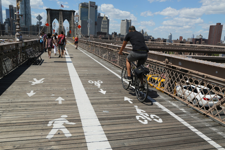 bicyclists: NEW YORK - JULY 19, 2016: Pedestrians and bicyclists crossing Brooklyn Bridge. About 4,000 pedestrians and 2,600 bicyclists cross the bridge every day.
