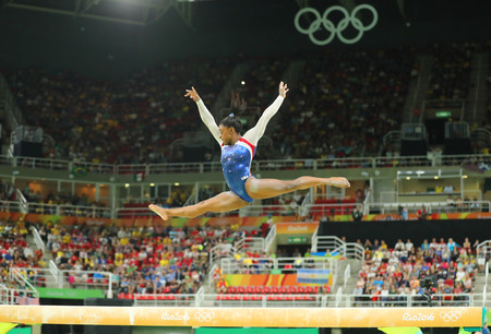 olympic games: RIO DE JANEIRO, BRAZIL – AUGUST 8, 2016: Olympic champion Simone Biles of United States competing on the balance beam at womens all-around gymnastics at Rio 2016 Olympic Games Editorial