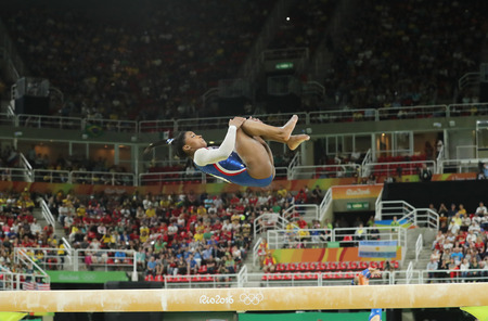simone: RIO DE JANEIRO, BRAZIL AUGUST 8, 2016: Olympic champion Simone Biles of United States competing on the balance beam at womens all-around gymnastics at Rio 2016 Olympic Games Editorial