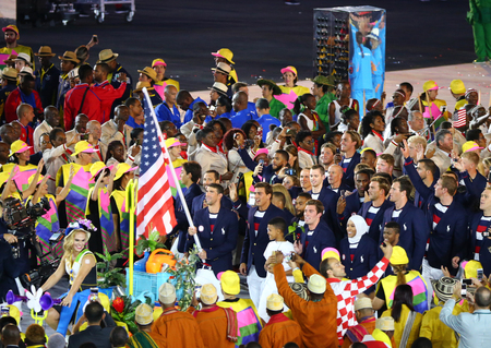 olympic symbol: RIO DE JANEIRO, BRAZIL - AUGUST 5, 2016: Olympic champion Michael Phelps carrying the United States flag leading the Olympic team USA in the Rio 2016 Opening Ceremony at Maracana Stadium