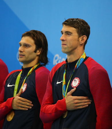 piscina olimpica: RIO DE JANEIRO, BRAZIL - AUGUST 13, 2016: USA Mens 4x100m medley relay team  Cory Miller (L) and  Michael Phelps celebrate victory at the Rio 2016 Olympic Games at the Olympic Aquatics Stadium