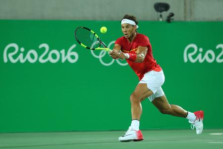 RIO DE JANEIRO, BRASIL - 12 de agosto, 2016: campeón olímpico Rafael Nadal de España en la acción durante los dobles de los hombres finales de los Juegos Olímpicos de Río 2016 en el Centro Olímpico de Tenis
