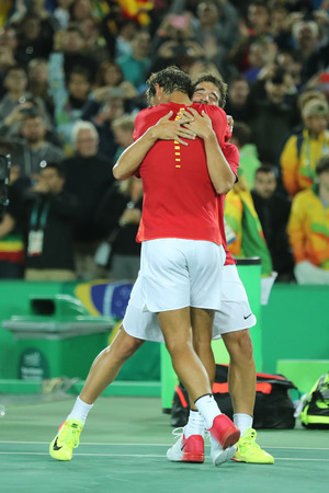 RIO DE JANEIRO, BRAZIL - AUGUST 12, 2016: Olympic champions Rafael Nadal (L) and Mark Lopez of Spain celebrate victory at mens doubles final of the Rio 2016 Olympic Games at the Olympic Tennis Centre