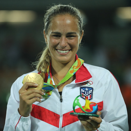 RIO DE JANEIRO, BRAZIL - AUGUST 13, 2016: Olympic champion Monica Puig of Puerto Rico during medal ceremony after victory at womens singles final of the Rio 2016 Olympic Games