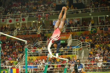 simone: RIO DE JANEIRO, BRAZIL - AUGUST 9, 2016: Olympic champion Simone Biles of United States competes on the uneven bars at womens team all-around gymnastics at Rio 2016 Olympic Games at Rio Olympic Arena