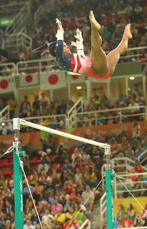 RIO DE JANEIRO, BRAZIL - AUGUST 9, 2016: Olympic champion Simone Biles of United States competes on the uneven bars at womens team all-around gymnastics at Rio 2016 Olympic Games at Rio Olympic Arena